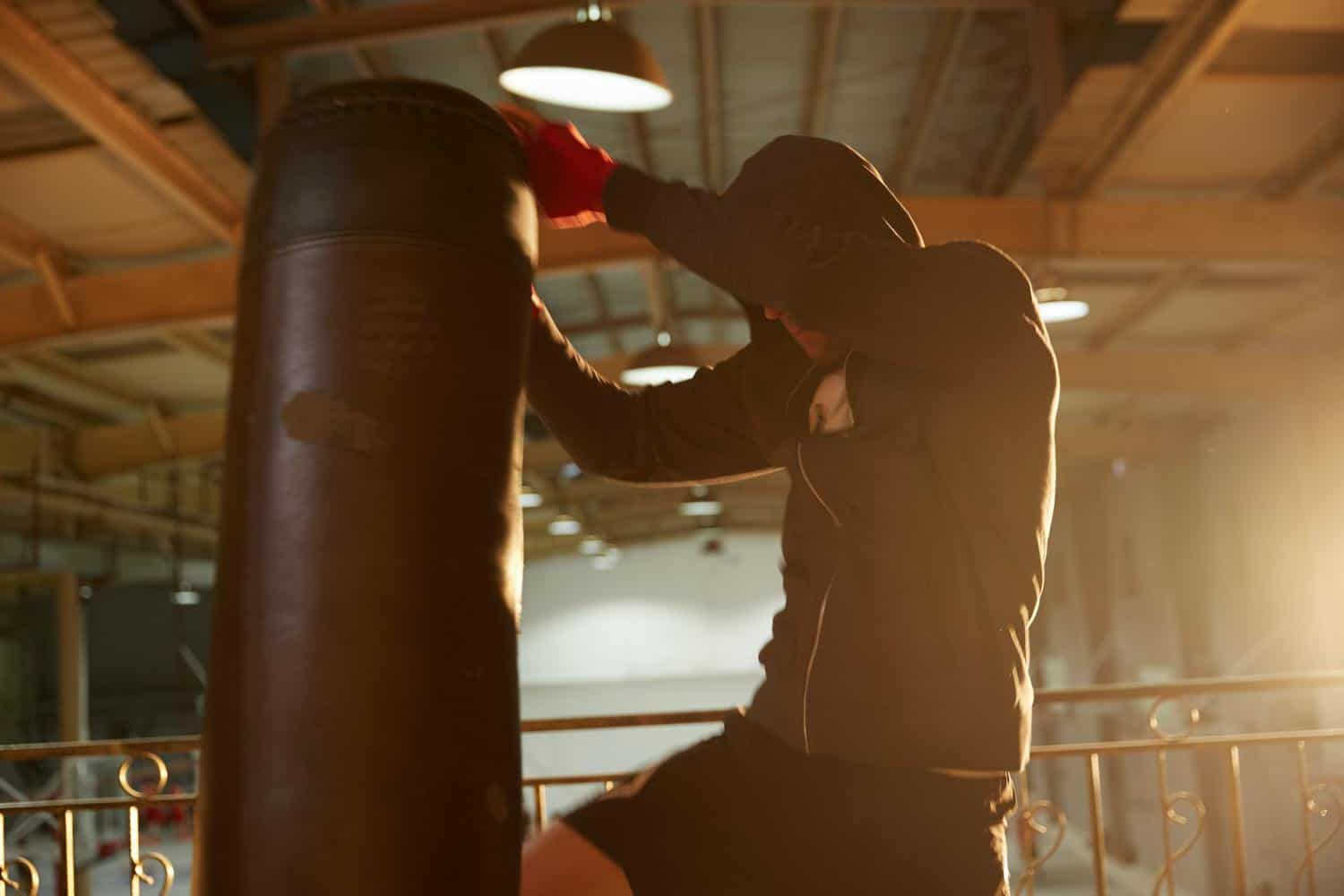 Man Kneeing Punching Bag